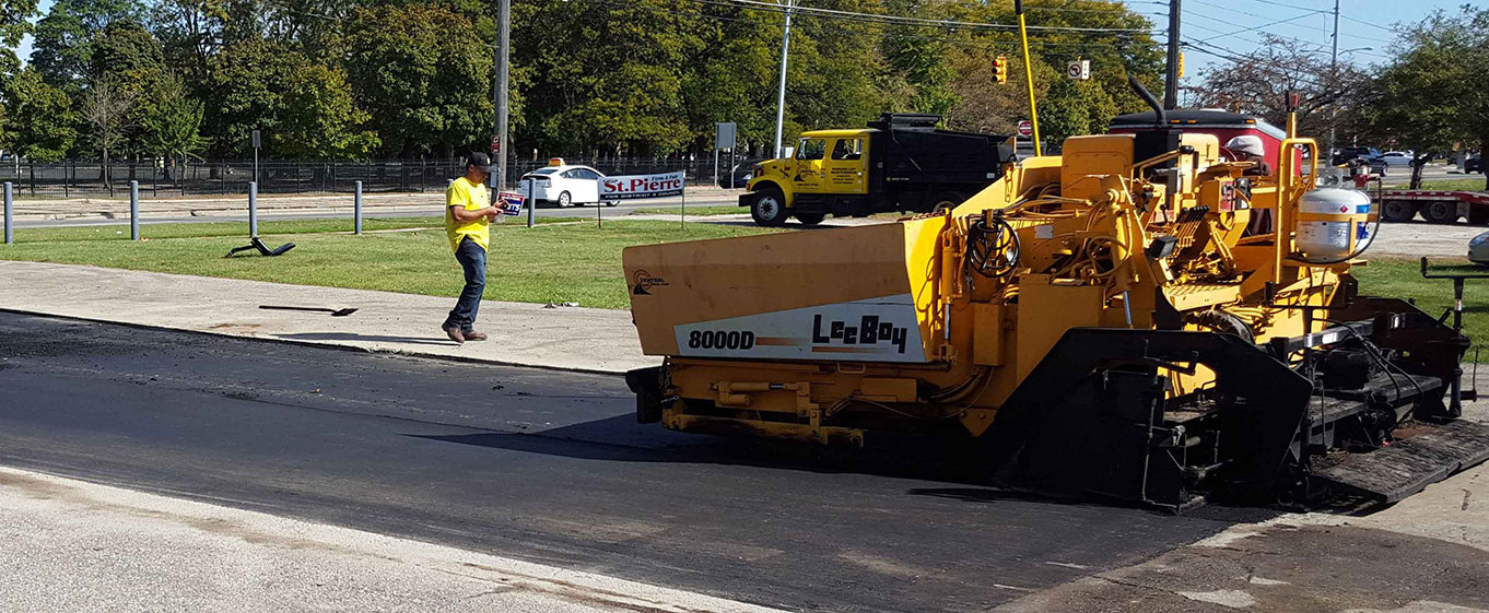 Central Seal Coat's most up to date asphalt spreader being used to repair a parking lot