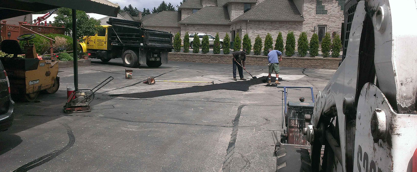 Central Seal Coat employees working on a Parking lot asphalt repair with a asphalt spreader