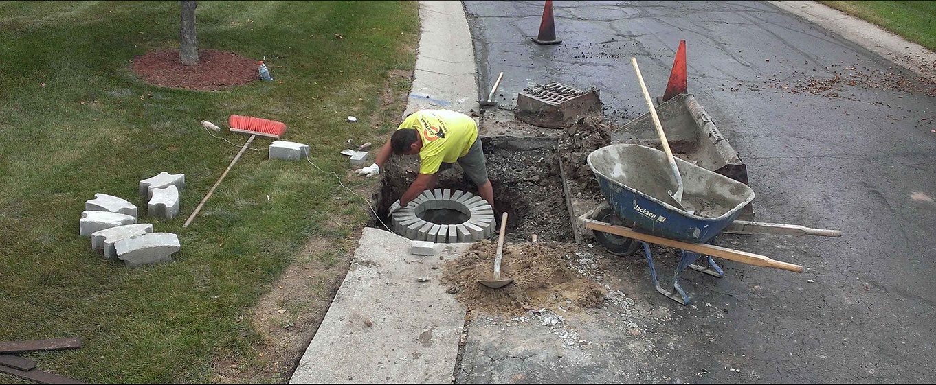 Central Seal Coat employee repairing a concrete catch basin